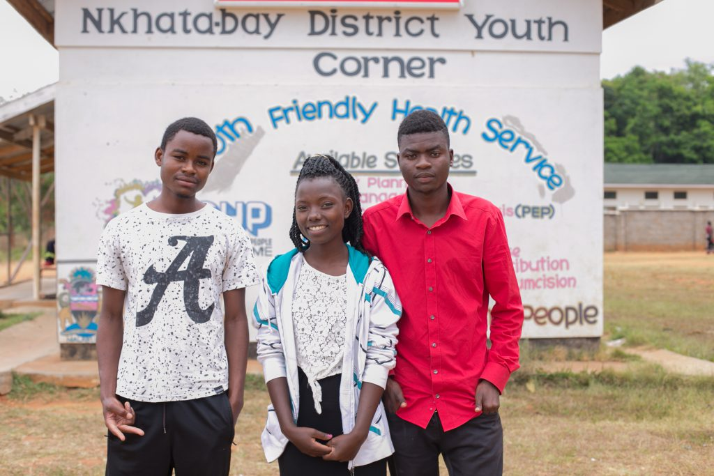 3 young people in Malawi in front of youth center